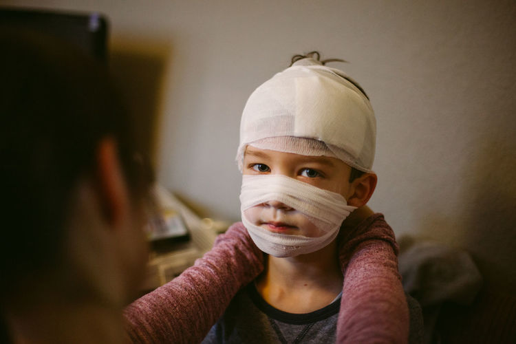 Portrait of boy with bandage on face at home