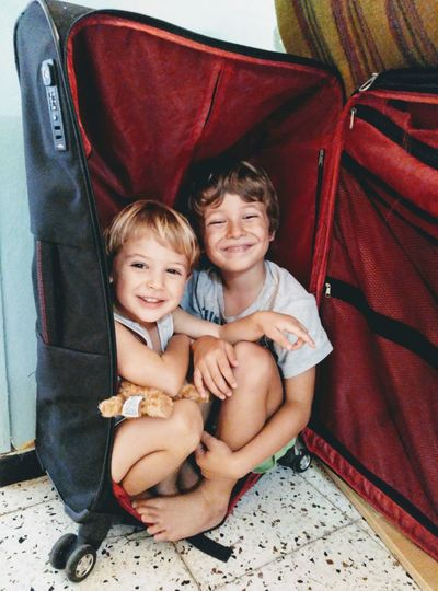 Portrait of smiling siblings sitting in suitcase at home