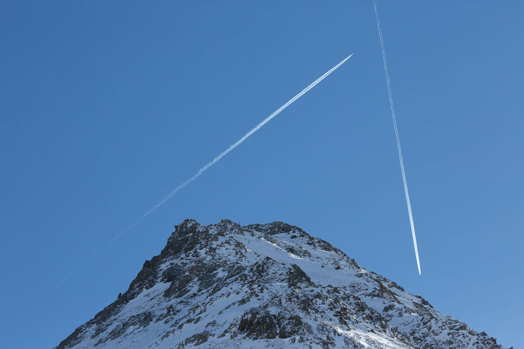 Low angle view of vapor trail and the european alps against clear blue sky