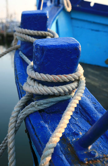 Close-up of rope tied on boat at harbor