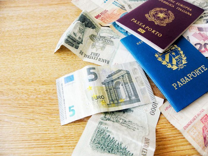High Angle View Paper Currency Table Indoors  Wood - Material No People Currency Close-up Day Light Wealth Finance Money Around The World Money Business Finance And Industry Passports Personal Documents Travel Destinations Preparing For Trip Currency Document Colours Red Passport Blue Passport
