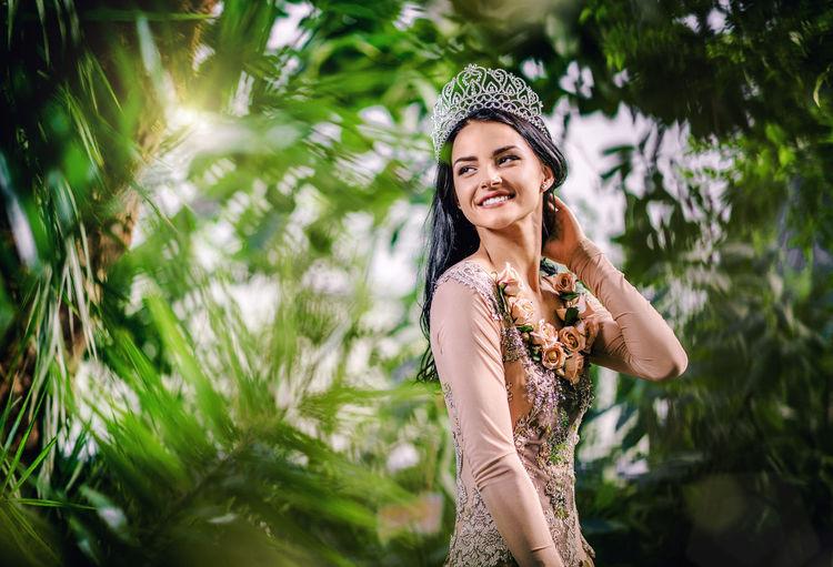 Smiling beautiful bride looking away while wearing crown at botanical garden