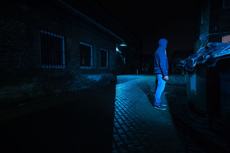 Side view of man standing on illuminated footpath at night