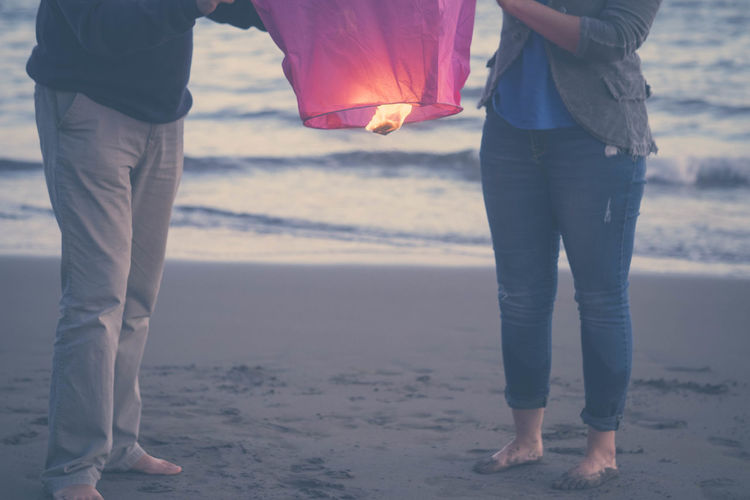 young couple on the beach with flying lantern on sunset barefoot Beach Bonding Couple - Relationship Day Focus On Foreground Friendship Human Leg Leisure Activity Lifestyles Love Low Section Men Nature Outdoors Real People Sand Sea Standing Togetherness Two People Vacations Water Women Young Women