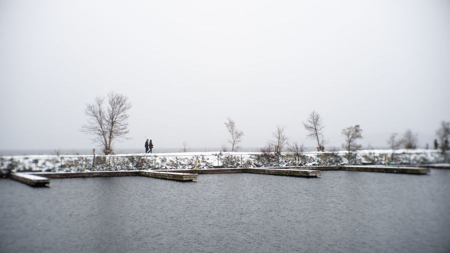 couple walks the shoreline on a snowy winter day Docks Winter Dock Walk In The Park Couple Walking Winter Walk Walking In The Snow Romantic Scenery Romantic Landscape Landscape Landcape_collection Street Photography Winter Sky Snow Snowy Sky Snowy Day In The Par Snow In The Sky Romantic Date Two People People In The Background People In The Distance