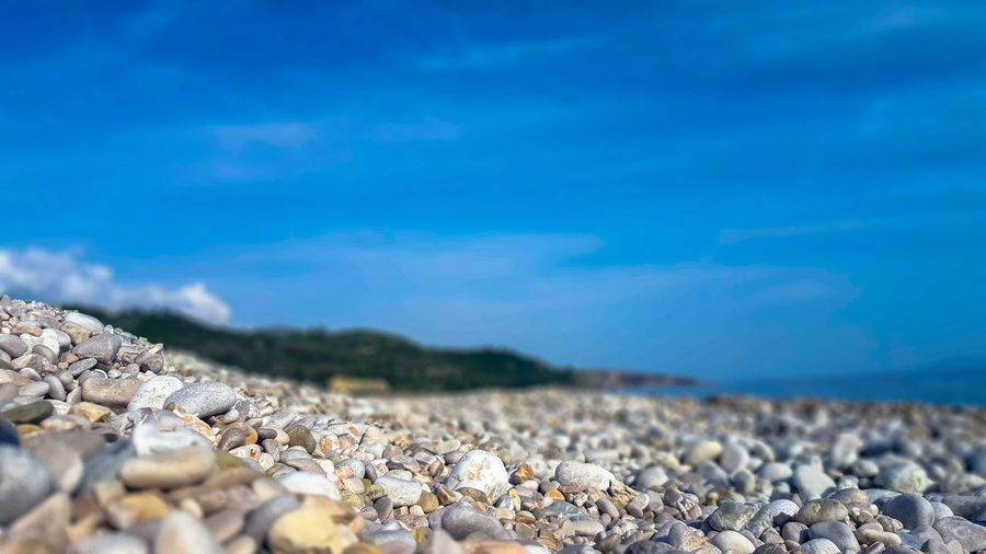Surface level of stones on beach against blue sky