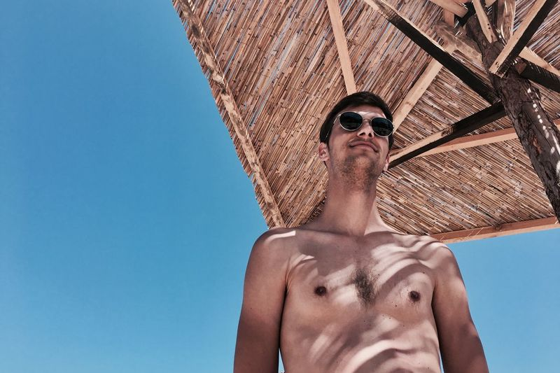 Low Angle View Of Shirtless Man Against Clear Blue Sky