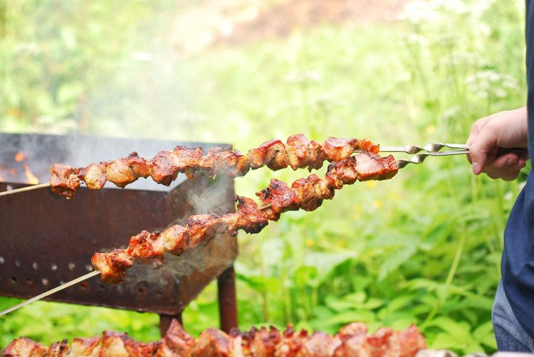 Cropped image of person hand on barbecue grill