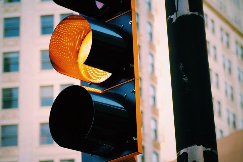 Close-up of illuminated stoplight against buildings