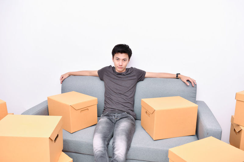 Box Box - Container Cardboard Cardboard Box Casual Clothing Container Copy Space Front View Indoors  Lifestyles Looking At Camera Men One Person Portrait Smiling Three Quarter Length Young Adult Young Men