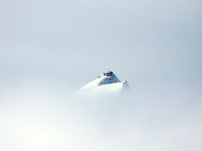 House On Top Of Snowcapped Mountain Against Clear Sky During Foggy Weather