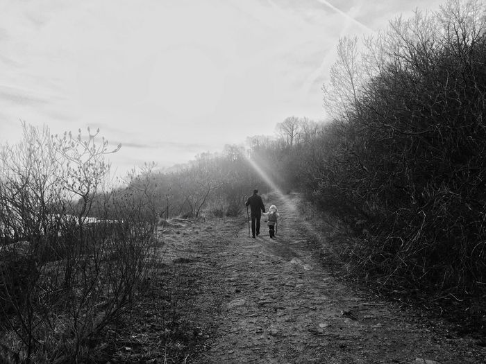 Rear View Of Father And Daughter Walking On Pathway Against Sky