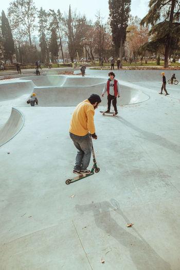 Rear view of people skateboarding in park