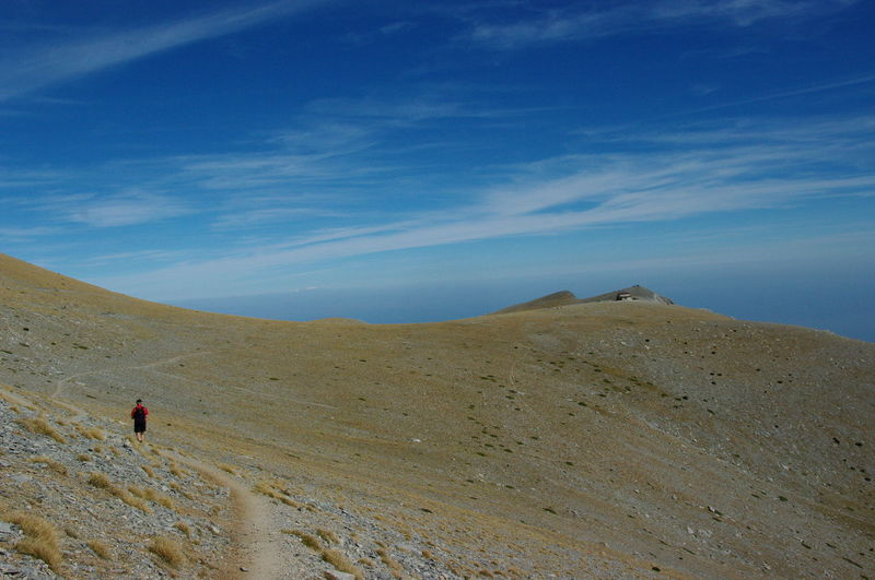 Man walking on mountain trail against blue sky