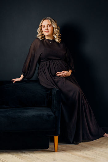 Portrait of pregnant woman sitting on sofa against black background