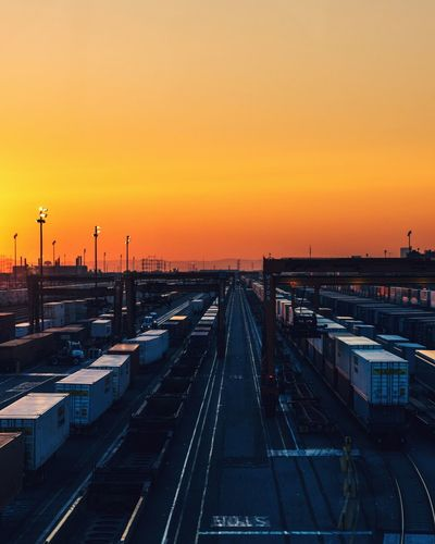 Cargo containers against orange sky during sunset