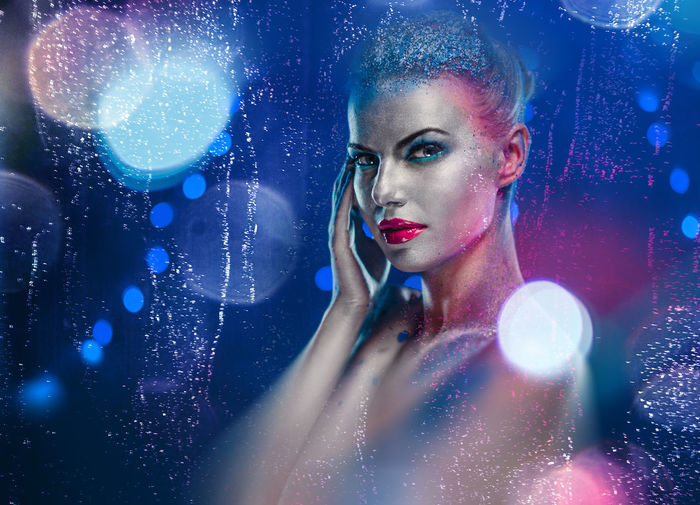 Portrait Of Naked Woman With Glitter Against Blue Background