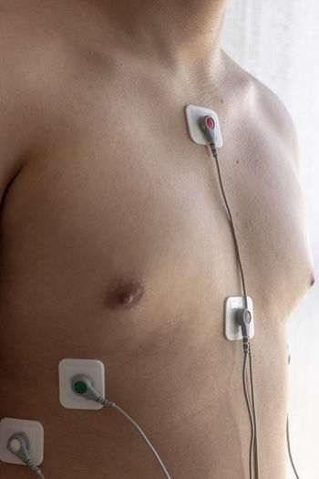 Midsection of shirtless man with medical equipment
