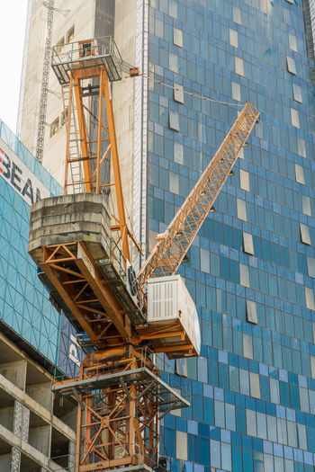 Low angle view of crane against building