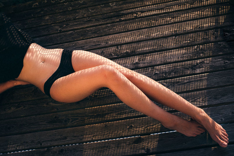 High Angle View Of Seductive Woman Lying Down On Wooden Floor