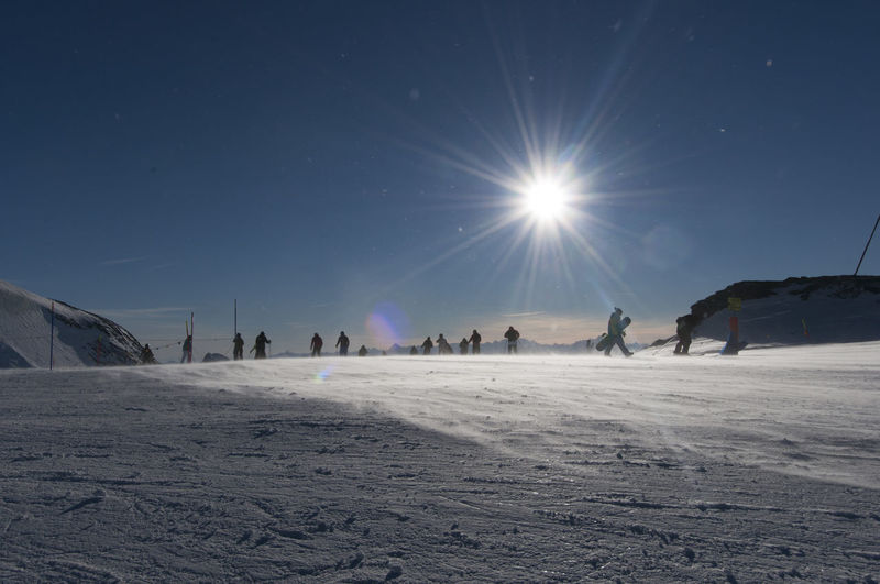 Group of people on snow covered land against bright sun