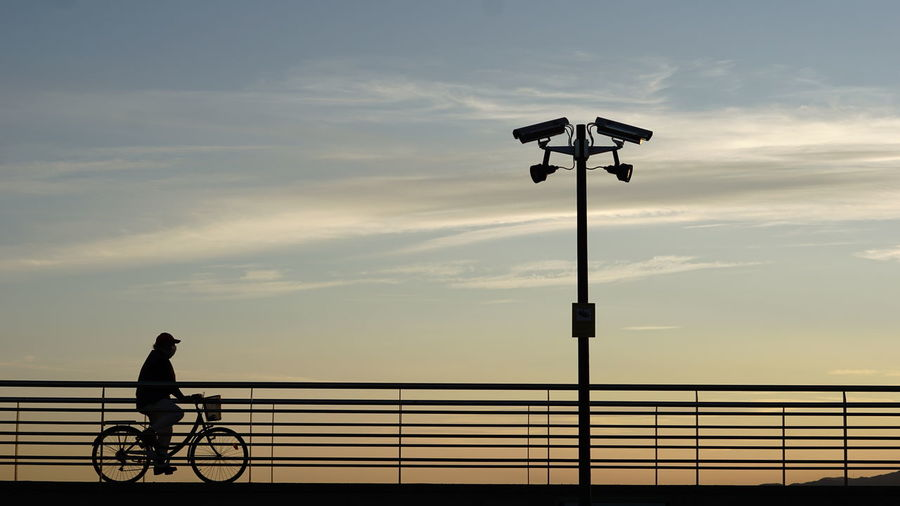 Silhouette man riding bicycle on street against sky
