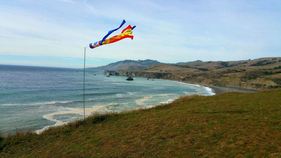 Colorful windsock! Directional and speed for paragliding off ocean cliffs. Windsock Red Blue Yellow White Ocean Cliff Paragliding Directional Speed Direction Information Sport Leisure Curve Atmospheric Zen Dramatic Golden Countryside Romantic Rural Water Flying Sea Beach Mid-air Sky Shore Fluttering