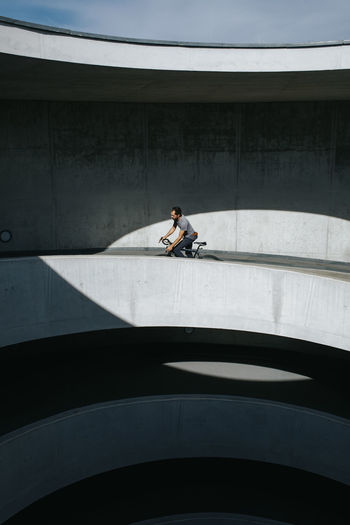 Man riding bicycle on bridge