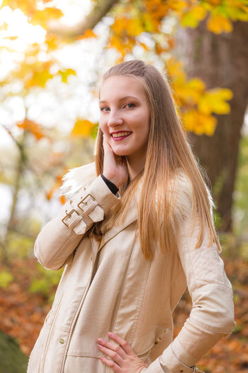 Portrait of young beautiful woman with straight blond hair standing against tree during autumn