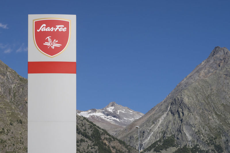 Street sign with the name Saas-Fee on it, a popular wintersports city in Switzerland with mountains and a blue sky on the background Saas Fee Switzerland City Village Tourism Tourist Destination Alps Mountain Sign Text Scenics - Nature Streetsign