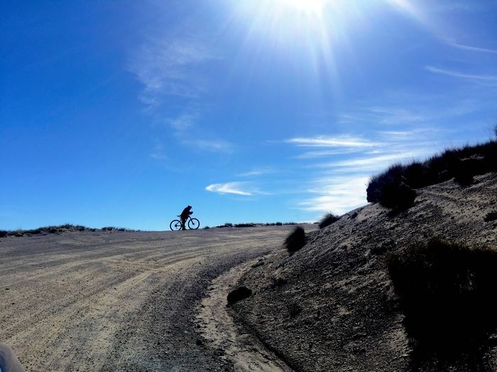 Man Riding Bicycle On Dirt Road Against Blue Sky