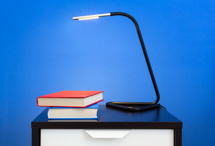 Low angle view of electric lamp on table against blue sky