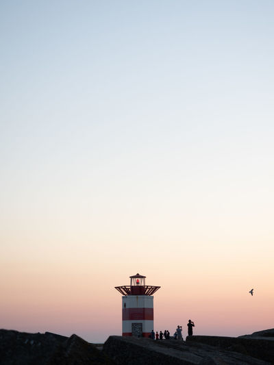 Silhouette building by sea against clear sky during sunset