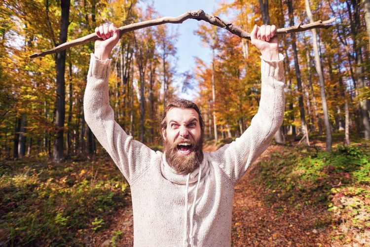 Portrait of bearded man holding stick screaming while standing against trees in forest