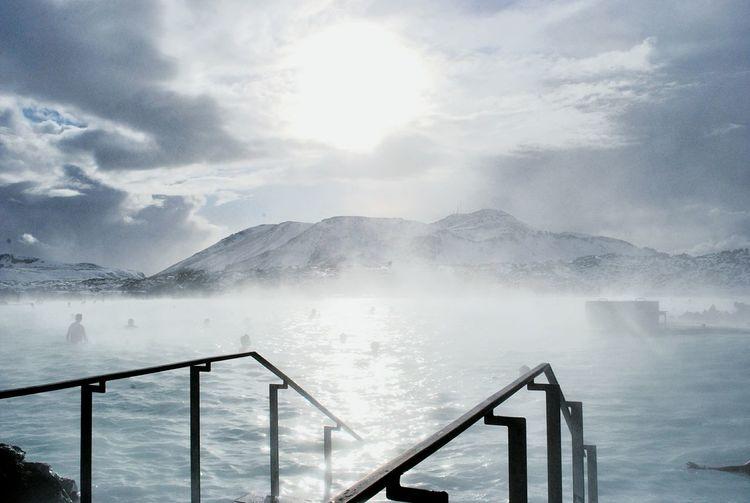 People in hot spring against sky