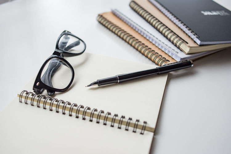 Close-up of spiral notebooks with eyeglasses and pen on table