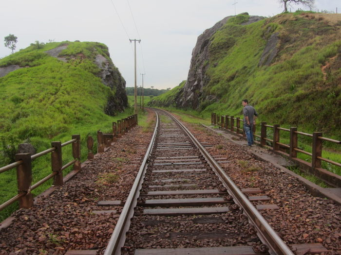 Beauty In Nature Day Full Length Green Color Growth Nature One Person Outdoors People Rail Transportation Railroad Track Real People Rural Scene Scenics Sky Standing The Way Forward Transportation Tree Lost In The Landscape