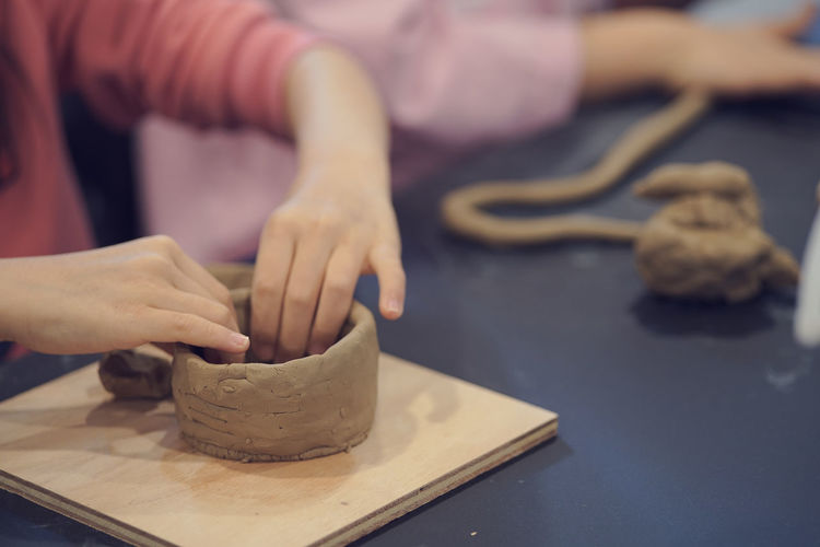Cropped Image Of Hands Making Pottery From Clay