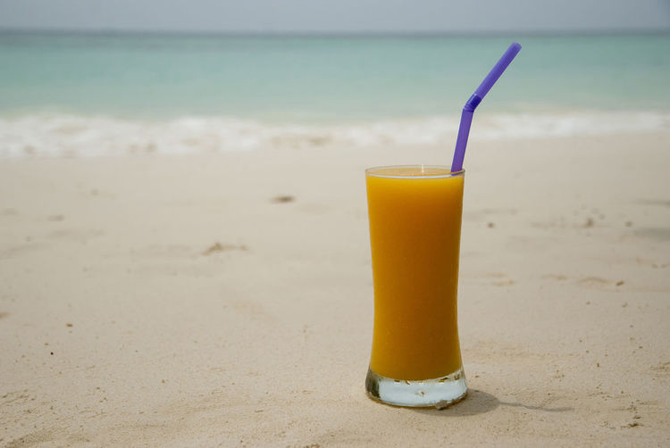 High angle view of fresh juice on sand at beach
