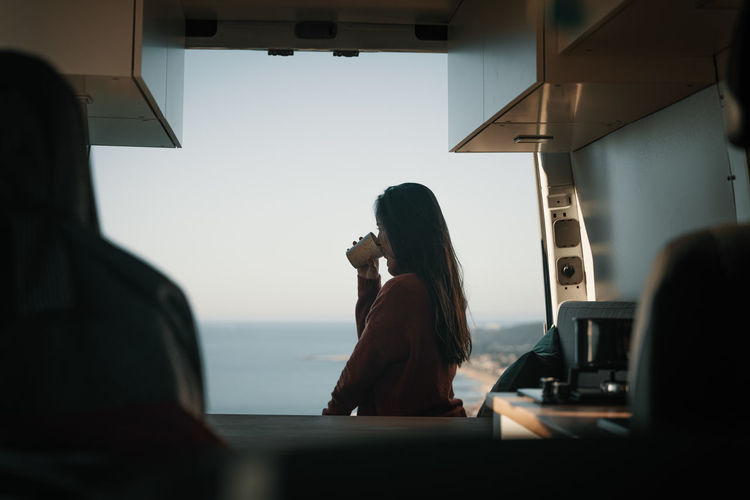 Rear view of woman sitting in bus drinking from cup