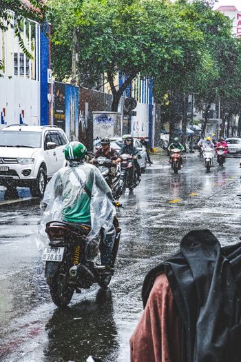 People riding motorcycle on wet street in rainy season