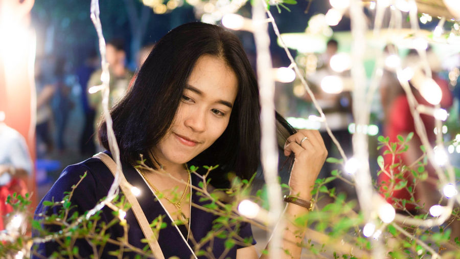 Close-up of smiling young woman looking away by plants in illuminated city