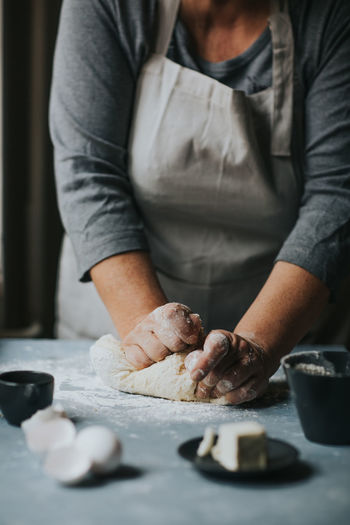 Midsection of woman kneading dough