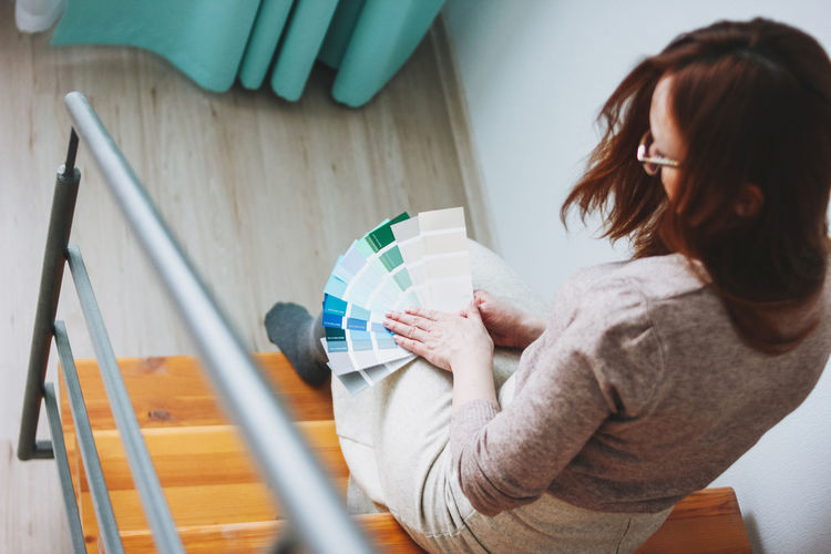 High angle view of woman looking at color swatches sitting on steps