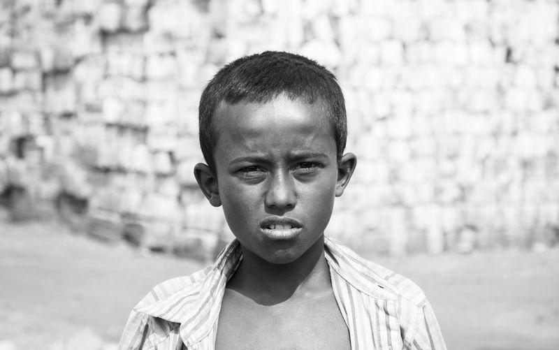 Portrait of poor boy standing on land