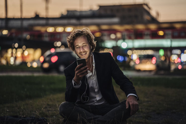Portrait of smiling young man sitting in city at night