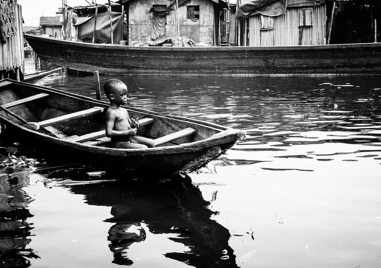Alone Lagos Makoko The Week on EyeEm Boy In A Boat Documentary Hardships Of Life Lagoon Mode Of Transport Mode Of Transportation Reflection Reportage Rowboat Streetphotography Transportation Water Water Street Watervillage Waterway Young Boy