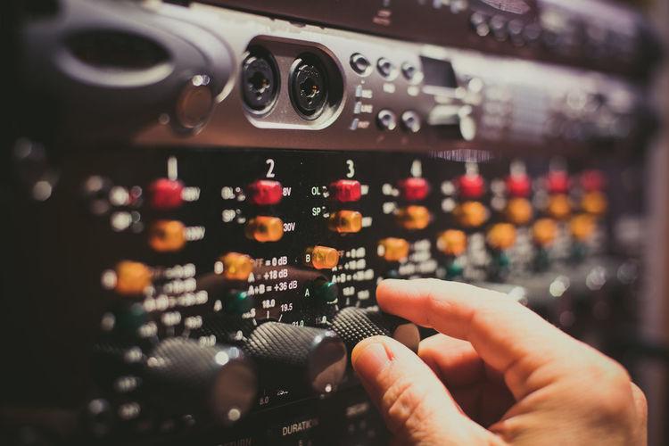 Close-up of human hand adjusting knob on audio amplifier