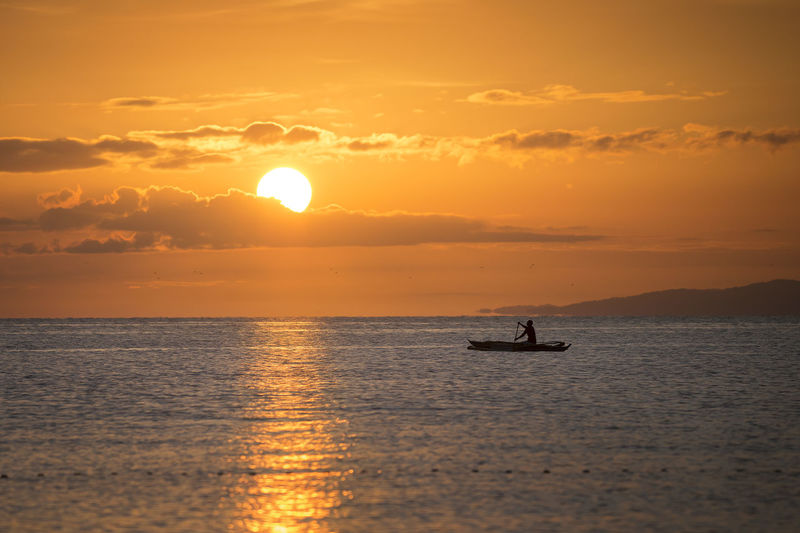 lonely fisherman in the morning Sun Waterfront Water Orange Color Tranquil Scene Horizon Sunrise Fisherman Fishing Boat Lonely Livelyhood Work Environment Tranquility Warm Row Silhouette Fishing Clouds Sea Scenics - Nature Beauty In Nature