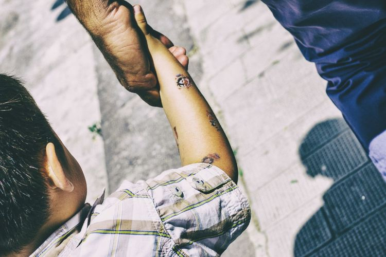 Cropped image of father holding son hand while walking on street during sunny day